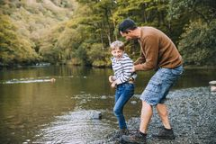 Don`t do it Dad!. Little boy and his father have been hiking and found a pond. His father is holding the boy, teasing to throw him in the water Stock Images