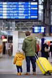 Little boy and his father in international airport or on railway station platform looking on information display. Travel, tourism, winter vacation and family Stock Photos
