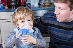 Little boy and his father making inhalation with nebuliser Royalty Free Stock Images