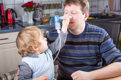 Little boy and his father making inhalation with nebuliser Stock Photos