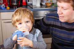Little boy and his father making inhalation Stock Photos