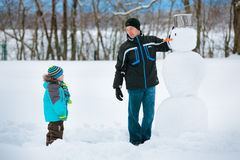 Little boy with his father making a snowman Royalty Free Stock Photos