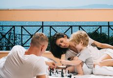Little boy and his father with mother playing chess.  Stock Images