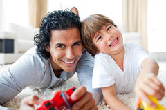 Little boy and his father playing video games. Animated little boy and his father playing video games lying on the floor Royalty Free Stock Image