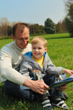 Little boy and his father are reading a book. Outdoor royalty free stock images