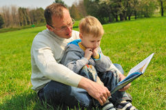 Little boy and his father are reading a book. Outdoor stock photos