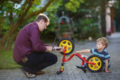 Little boy and his father repairing bicycle wheel outdoors. Stock Photography