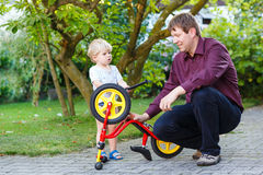 Little boy and his father repairing bicycle wheel outdoors. Royalty Free Stock Image