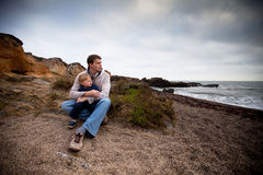 Little boy in his father's arms. Sitting on the beach on a stormy day royalty free stock image