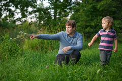 Little boy and his father sitting on grass in summer forest Stock Photos