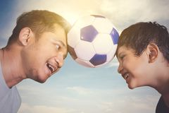 Little boy and his father playing football together. Little boy and his father with a soccer ball on their heads while playing football together royalty free stock images
