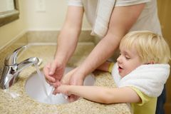 Little boy and his father washing their hands with soap in bathroom together. Hygiene for little child stock photo