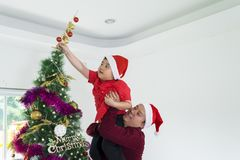 Asian boy and father decorate Christmas tree. Little boy and his father work together to decorate a Christmas tree at home royalty free stock photography