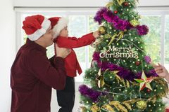 Boy and his father decorating Christmas tree. Little boy and his father work together to decorate a Christmas tree at home royalty free stock images