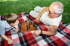 Little boy and his grandfather play chess in the park stock images