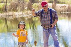 Little Boy and His Grandpa Fishing. A cute little boy catching a fish with his Grandpa Royalty Free Stock Photo