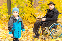 Little boy with his handicapped grandfather Royalty Free Stock Photos