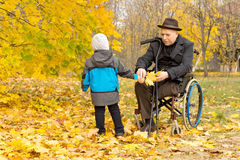 Little boy with his handicapped grandfather Royalty Free Stock Images