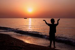 Little boy with his hands up meets the dawn. Little boy with his hands up meets the dawn and holds the horizon Royalty Free Stock Photos