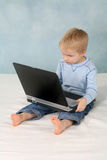 Little Boy and His Laptop. A cute preschool boy sits on a mattress and plays with a laptop computer that is almost as large as he is stock image
