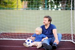 Little boy and his middle age father having fun playing a soccer/football game on summer day Royalty Free Stock Photography