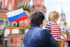 Little boy and his middle age father holding russian flag Stock Photos