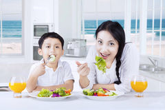 Little boy and his mom enjoy salad Stock Images