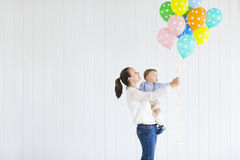 Little boy with his mom holding a bunch of colored balloons Stock Image