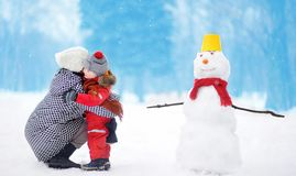 Little boy with his mother/babysitter/grandmother building snowman in snowy park. Active outdoors leisure with children in winter. Kid embrace with his mother stock images