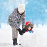 Little boy with his mother/babysitter/grandmother building snowman in snowy park. Active outdoors leisure with children in winter. Kid during stroll in a snowy stock photography