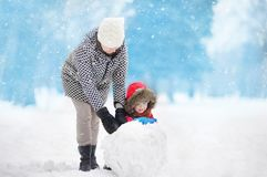 Little boy with his mother/babysitter/grandmother building snowman in snowy park Stock Image