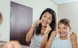 Mother and son cleaning teeth with dental floss. Little boy with his mother in bathroom cleaning teeth with dental floss. Woman with son looking in mirror and Stock Image