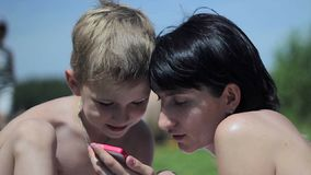 Little boy with his mother at a beach playing with a smartphone. Slowmotion stock video footage