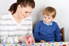 Little boy and his mother being happy about selfmade Easter eggs Stock Photo
