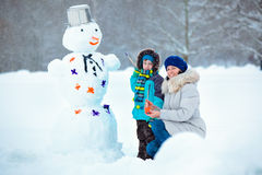 Little boy with his mother painting a snowman Royalty Free Stock Image