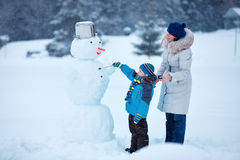 Little boy with his mother painting a snowman Stock Image