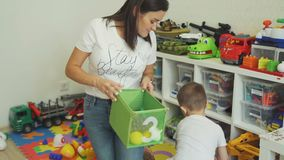 Little Boy Putting Toys into Box with his Mother stock video footage