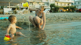 Little boy and his mother playing on the beach stock footage