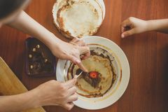 A little boy with his mother preparing together a breakfast. Mother and son smearing chocolate cream to thin pancakes. Free space. A little boy with his mother stock photo