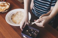A little boy with his mother preparing together a breakfast. Mother and son smearing chocolate cream to thin pancakes. Free space. A little boy with his mother royalty free stock photos