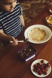 A little boy with his mother preparing together a breakfast. Mother and son smearing chocolate cream to thin pancakes. Free space. A little boy with his mother stock image