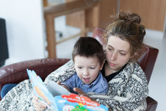 Little boy and his mother reading a story book Stock Photography