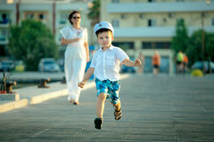 Little boy and his mother running at jetty Royalty Free Stock Photography