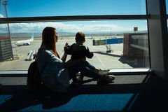 Little boy and his mother sitting in an airport Stock Photo