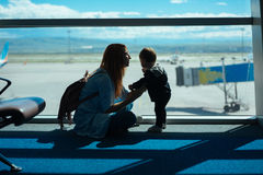 Little boy and his mother sitting in an airport Royalty Free Stock Photography