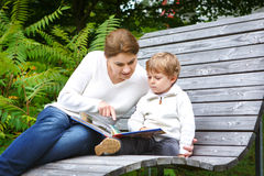 Little boy and his mother sitting on bench in park and reading b Stock Photos