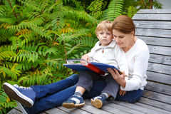 Little boy and his mother sitting on bench in park and reading b Royalty Free Stock Photos