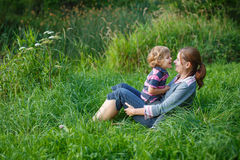 Little boy and his mother sitting on grass in summer forest Stock Photography
