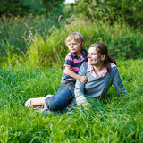 Little boy and his mother sitting on grass in summer forest Royalty Free Stock Images