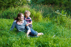 Little boy and his mother sitting on grass in summer forest Stock Photos